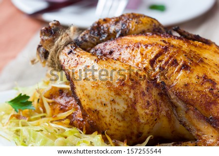 Roasted whole chicken with golden crust and garnish of stewed cabbage - stock photo