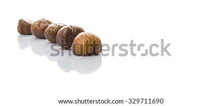 Roasted whole peeled chestnut over white background