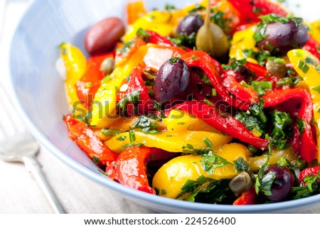 Roasted yellow and red bell pepper salad with capers and olives in a blue bowl on a white background. Grilled vegetables. - stock photo