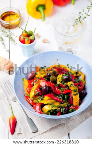 Roasted yellow and red bell pepper salad with capers and olives in a blue bowl on a white background. Grilled vegetables