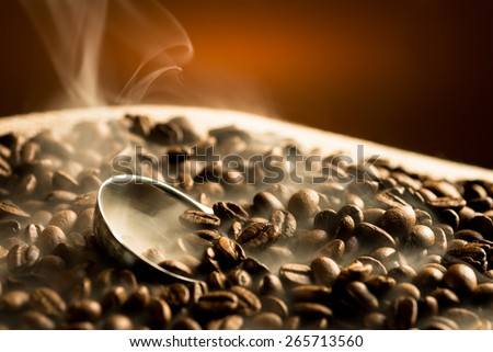 Roasting coffee beans with smoke on dark background - stock photo