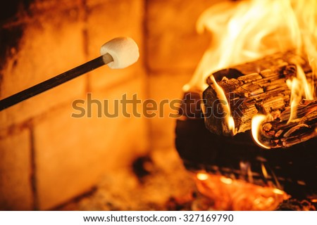 Roasting marshmallows by the fire. Cozy chalet home with fireplace decorated with traditional Christmas ornaments. Cozy relaxed magical atmosphere in a chalet. Holiday concept. - stock photo