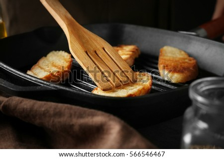 Roasting sliced bread on pan, closeup