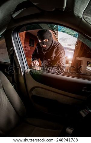 Robber and the car thief in a mask opens the door of the car and hijacks the car. - stock photo