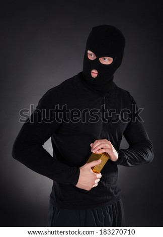 Robber disguised in a black balaclava holding a gold bullion bar as he makes his getaway from a heist with the loot through the darkness - stock photo