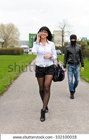 Robber follows his victim at daylight on the street - stock photo