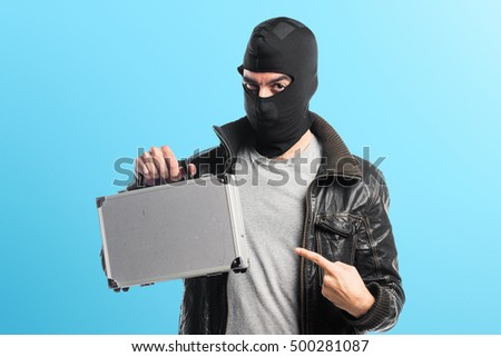 Robber holding a briefcase over colorful backgound