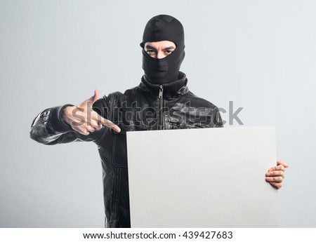 Robber holding an empty placard over grey background