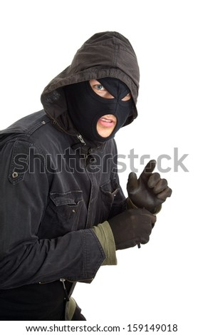 Robber in a black mask sneaking inside