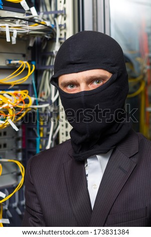 robber in black mask hack server room unauthorized downloading data on laptop - stock photo