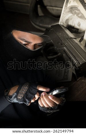 Robber man use smart phone with gun and money on background.