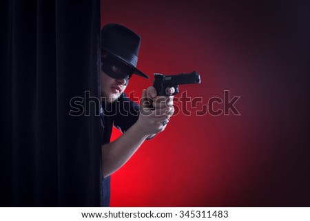 robber or bandit in a mask shoots a gun.
