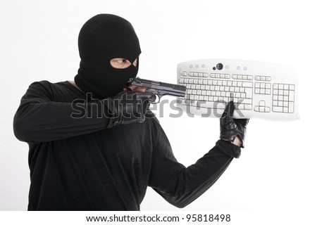 robber pointing a pistol at a computer keyboard - stock photo