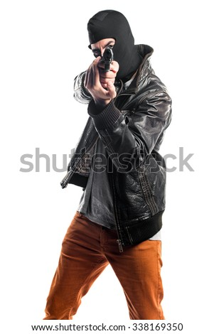 Robber shooting with a pistol - stock photo