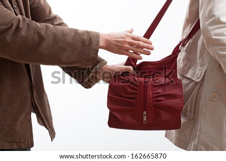Robber trying to steal a woman purse on the street - stock photo