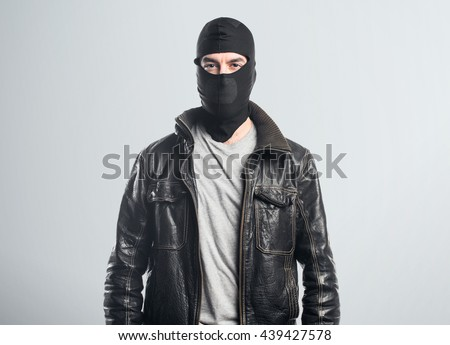 Robber wearing a leather jacket  over grey background