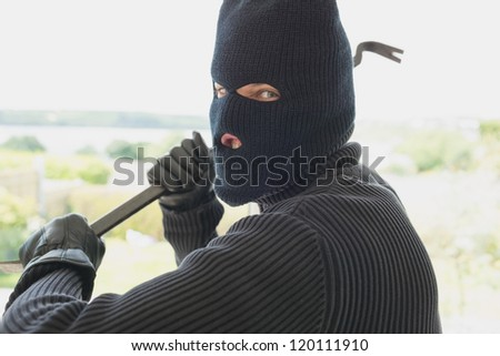 Robber with a crow bar in a home - stock photo