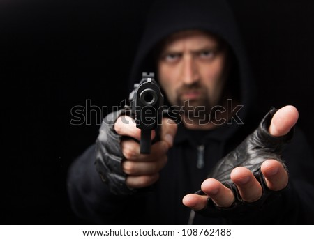 Robber with gun holding out hand against a black background - stock photo