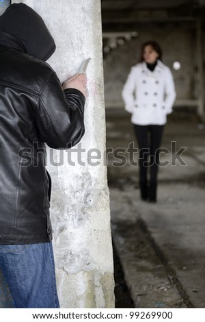 Robber with knife waiting for girl around the corner