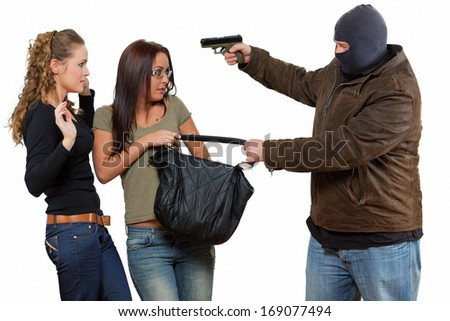 Robbery / Bad guy is robbering a two young women with a gun - stock photo