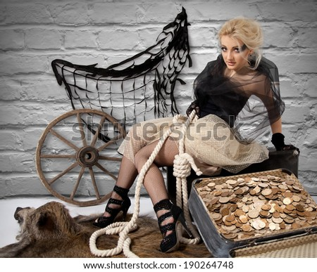 Robbery Girl is sitting on a suitcase with money which she had stolen - stock photo