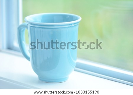 Robinâ??s egg blue mug on windowsill.  Blurred background with room for text.