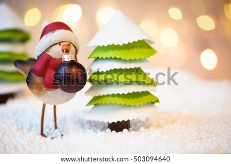 Robin with Christmas ball in a forest, Christmas lights in a background