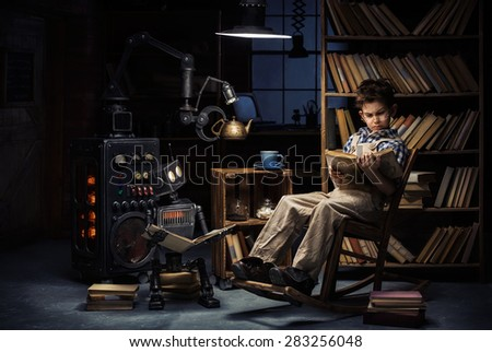 Robot-child and the mechanic and inventor read books in the studio late at night - stock photo