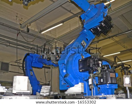 Robot in standby pose waiting for next work step in the production line. - stock photo