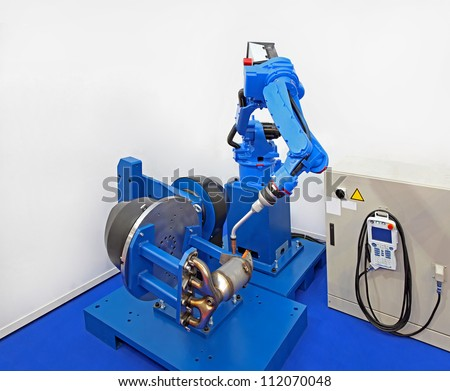 Robot welder manufacturing car parts in factory - stock photo