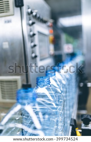 Robotic factory line for processing and bottling of pure spring water into canisters and bottles. Selective focus.