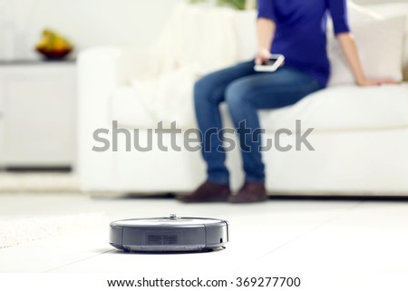 Robotic vacuum cleaner cleaning the room while woman sitting on sofa, closeup - stock photo