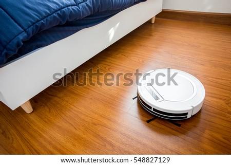Robotic Vacuum Cleaner On Laminate Wood Stock Photo 548827129