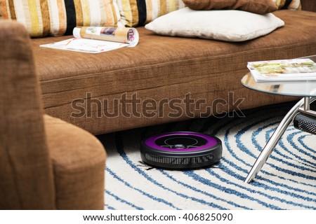 robotic vacuum cleaner on the carpet - stock photo