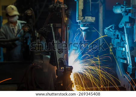 robots welding in a car factory - stock photo