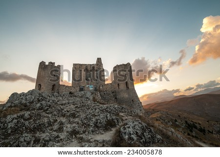 Rocca Calascio medieval ruins castle: the highest castle in Italy in the sunset light with orange clouds - stock photo