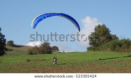 ROCCA PRIORA, ITALY - NOVEMBER 1, 2016: paragliding lesson, a paraglider landing after a training flight