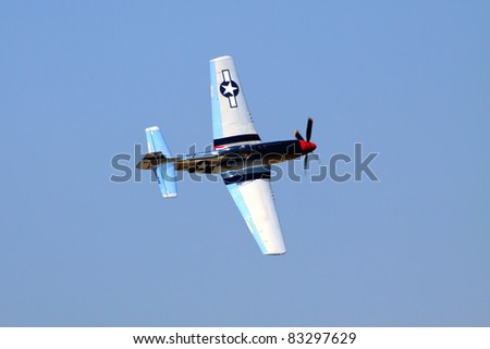 ROCHESTER - JULY 17: A WWII era P-51 Mustang fighter airplane flying during a performance at an airshow in Rochester, NY on July 17, 2011.  The propeller plane is speeding through a clear blue sky. - stock photo