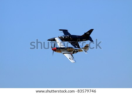 ROCHESTER, NY - JULY 17: A WWII era P-51 Mustang fighter and F-9 jet trainer airplanes flying during a performance at an airshow in Rochester, New York on July 17, 2011. - stock photo