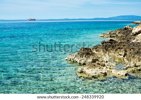 Rock and sea with boat on the horizon - stock photo