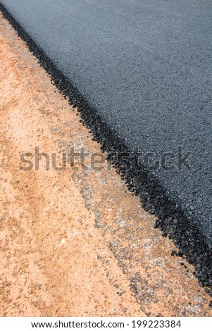 Rock and soil material on the new paved road - stock photo