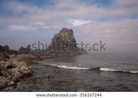 Rock at the Cape in the sea. Koni peninsula. Cape Taran. The Sea of Okhotsk. Magadan Region. Russia.