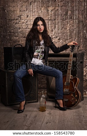 Rock babe in leather jacket with electric guitar