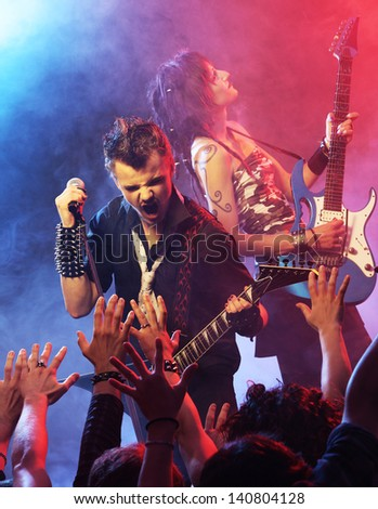 Rock band performing on stage - stock photo