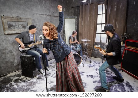 Rock band performs during shooting video clip - stock photo