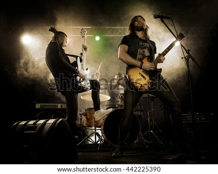 rock band performs on stage guitarist stock photo
