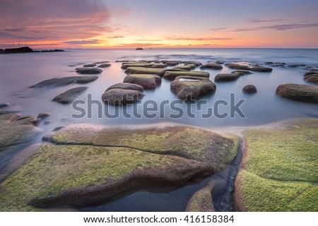 Rock boulders with green moss seascape at Tindakon Dazang Beach.  - stock photo