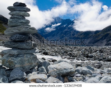 Rock cairn in Hooker Valley on a trail leading to Aoraki  Mount Cook  highest peak of Southern Alps  an icon of New Zealand partially covered in clouds - stock photo