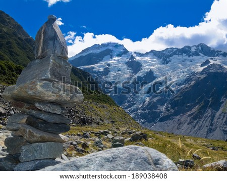 Rock cairn in Hooker Valley on a trail leading to Aoraki, Mount Cook, highest peak of Southern Alps an icon of New Zealand partially covered in clouds - stock photo