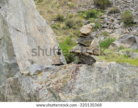 Rock cairn in the background of mountain slop, texture. Stones with lichen. Wet and cloudy weather. Summer, Mountain Altai region.